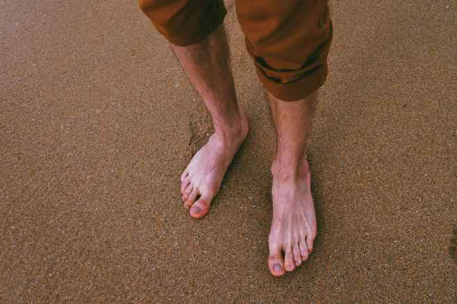 close up photo of person standing on seashore