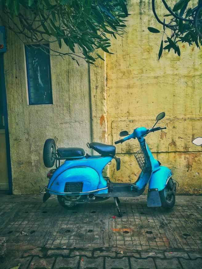 teal motor scooter on the street